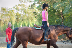 young horse rider taking a riding lesson