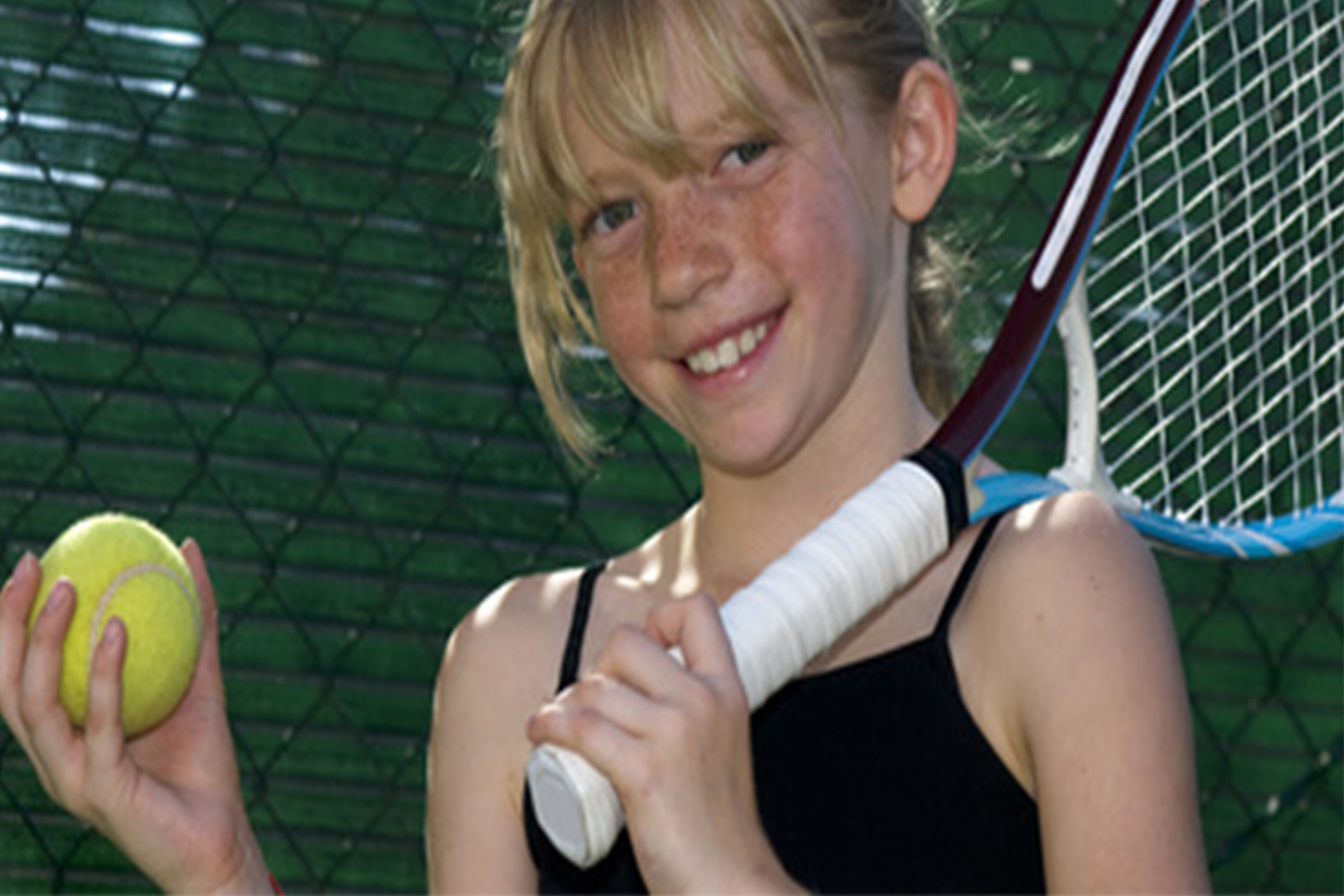 young girl with tennis racket and tennis ball