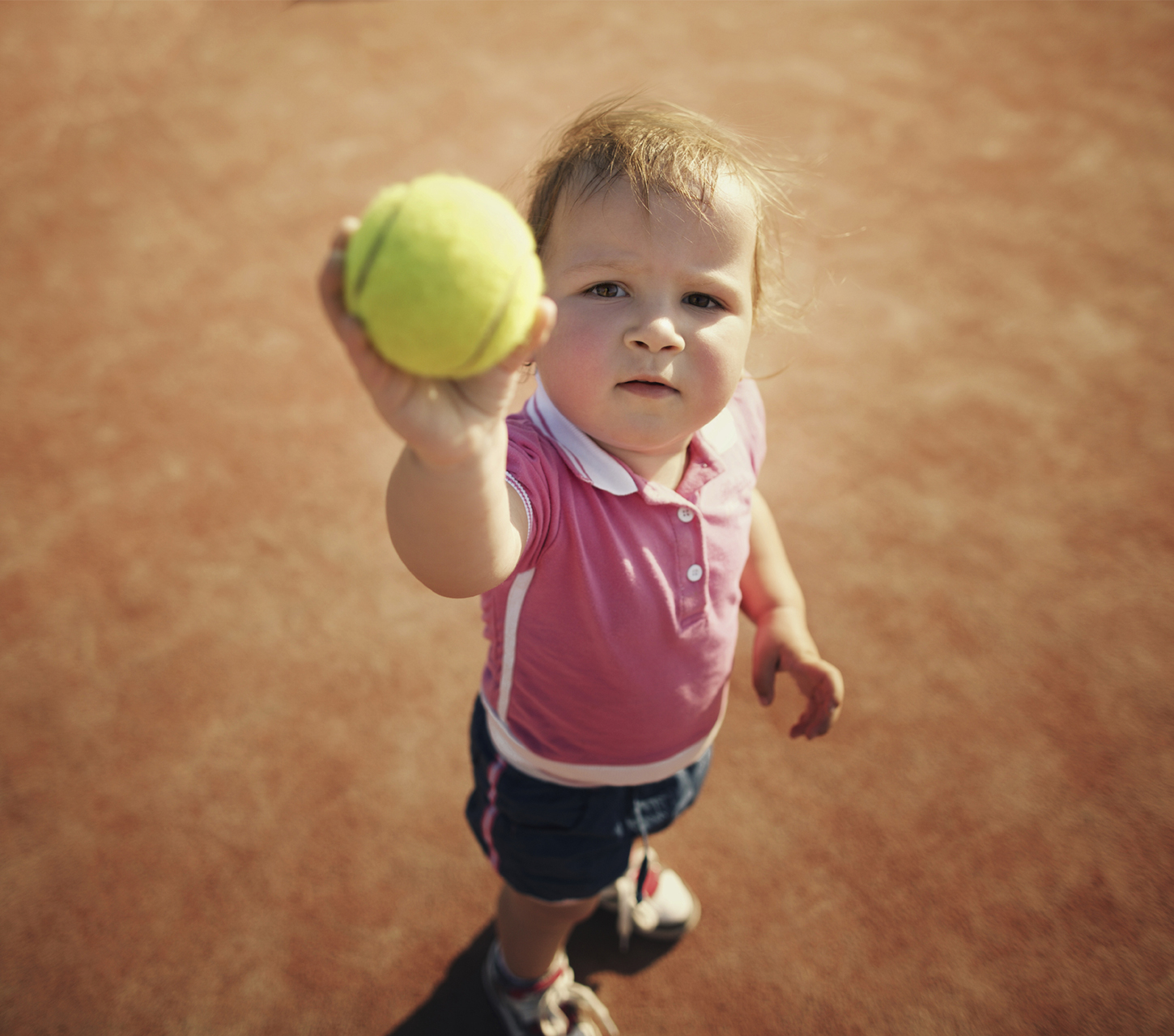 young girl holding up a tennis ball