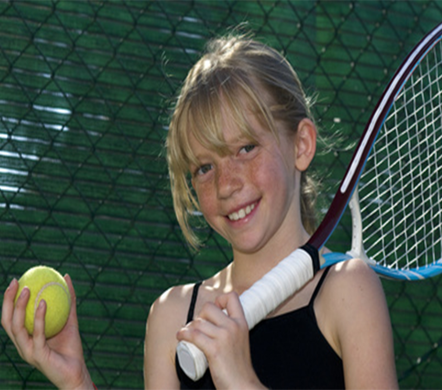 young girl with tennis racket and ball